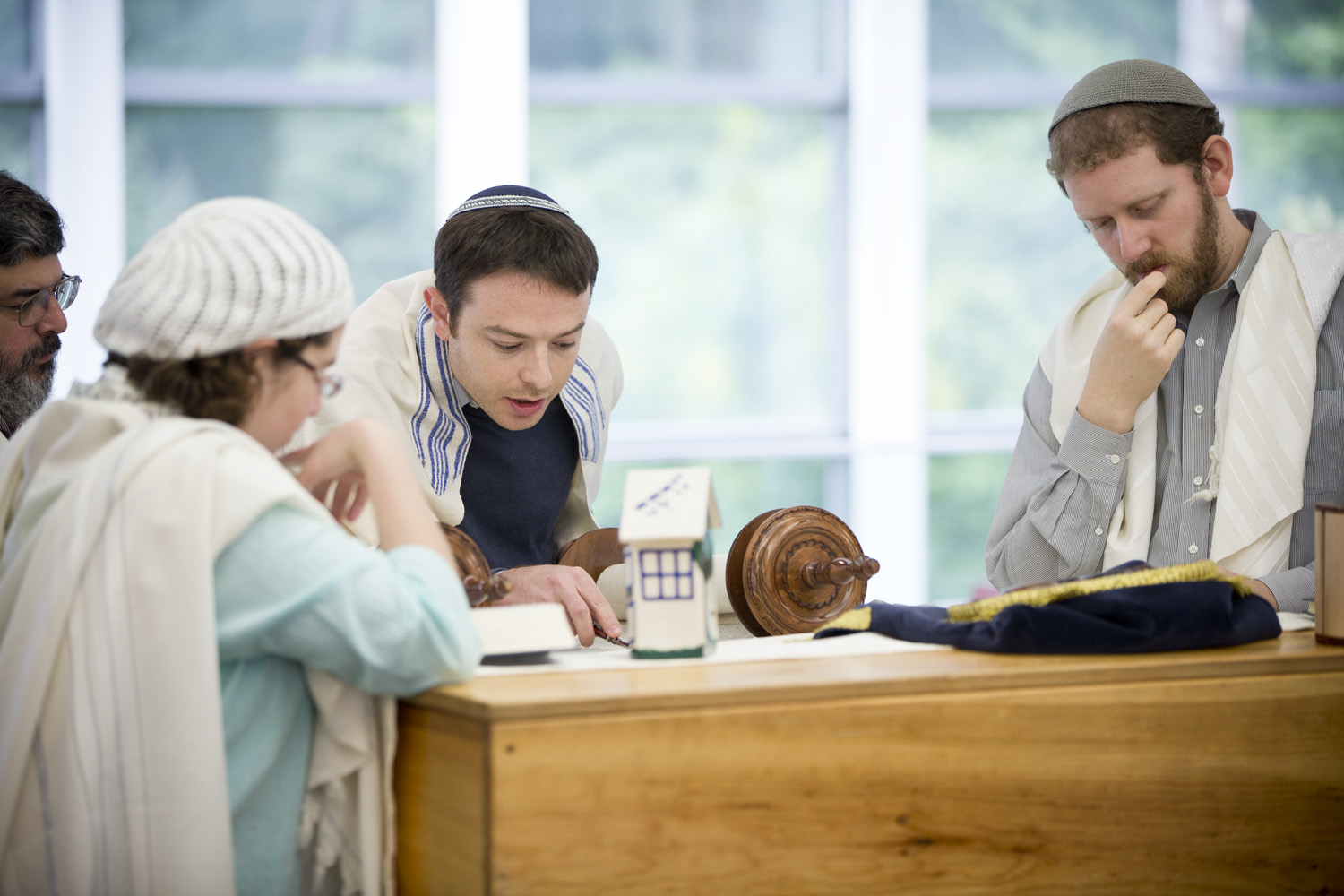 Four Rabbinical students leaning in, looking over a torah scroll.