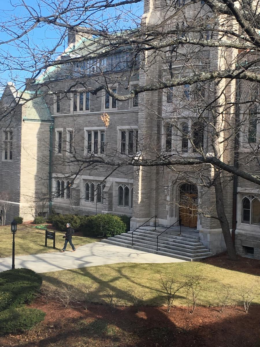 Boston College Stokes Hall. Tree without leaves in the foreground. Person walking out of the building.