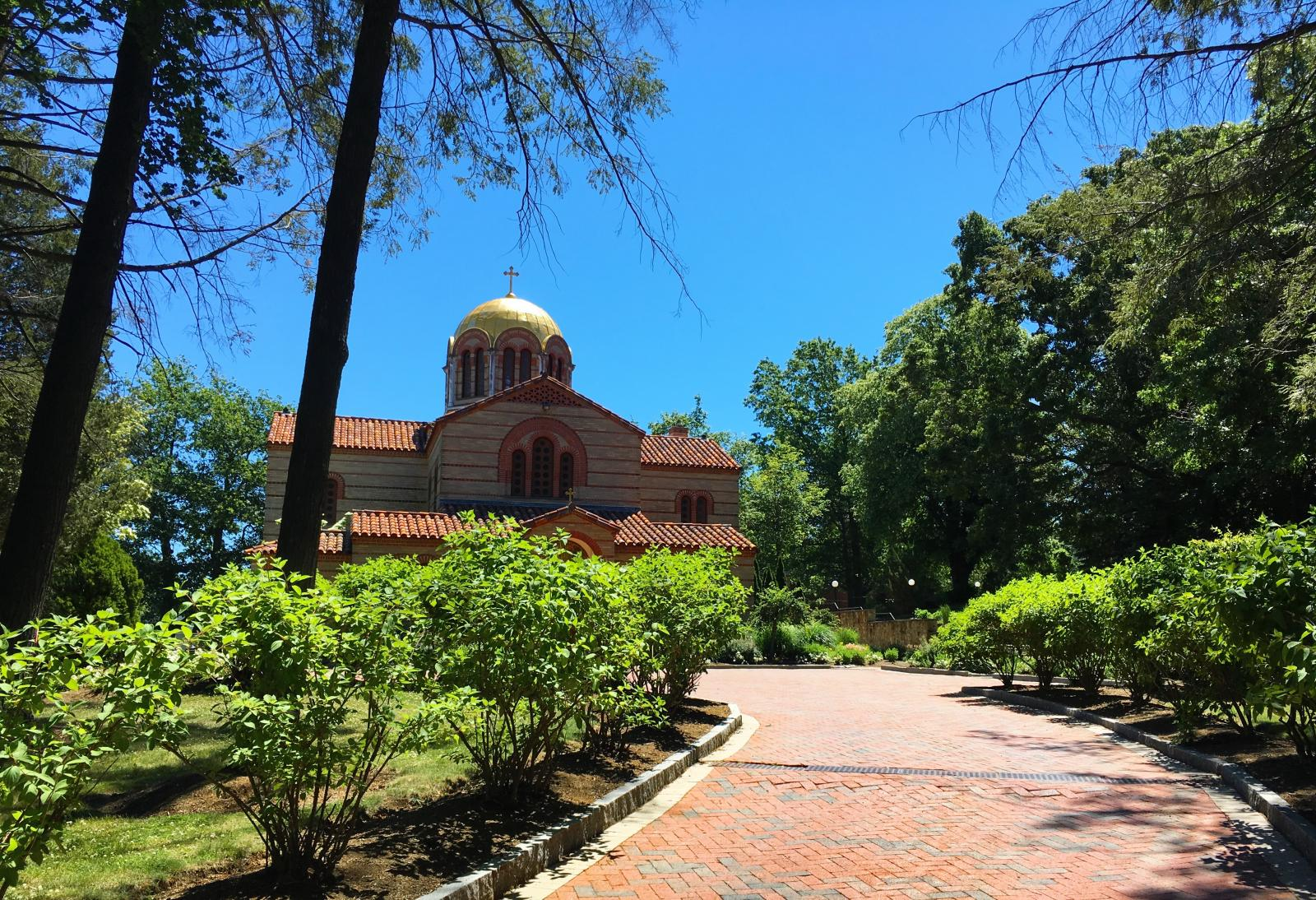 Orthodox church with golden dome and rust colored trim. Green trees. Cobblestone walkway.