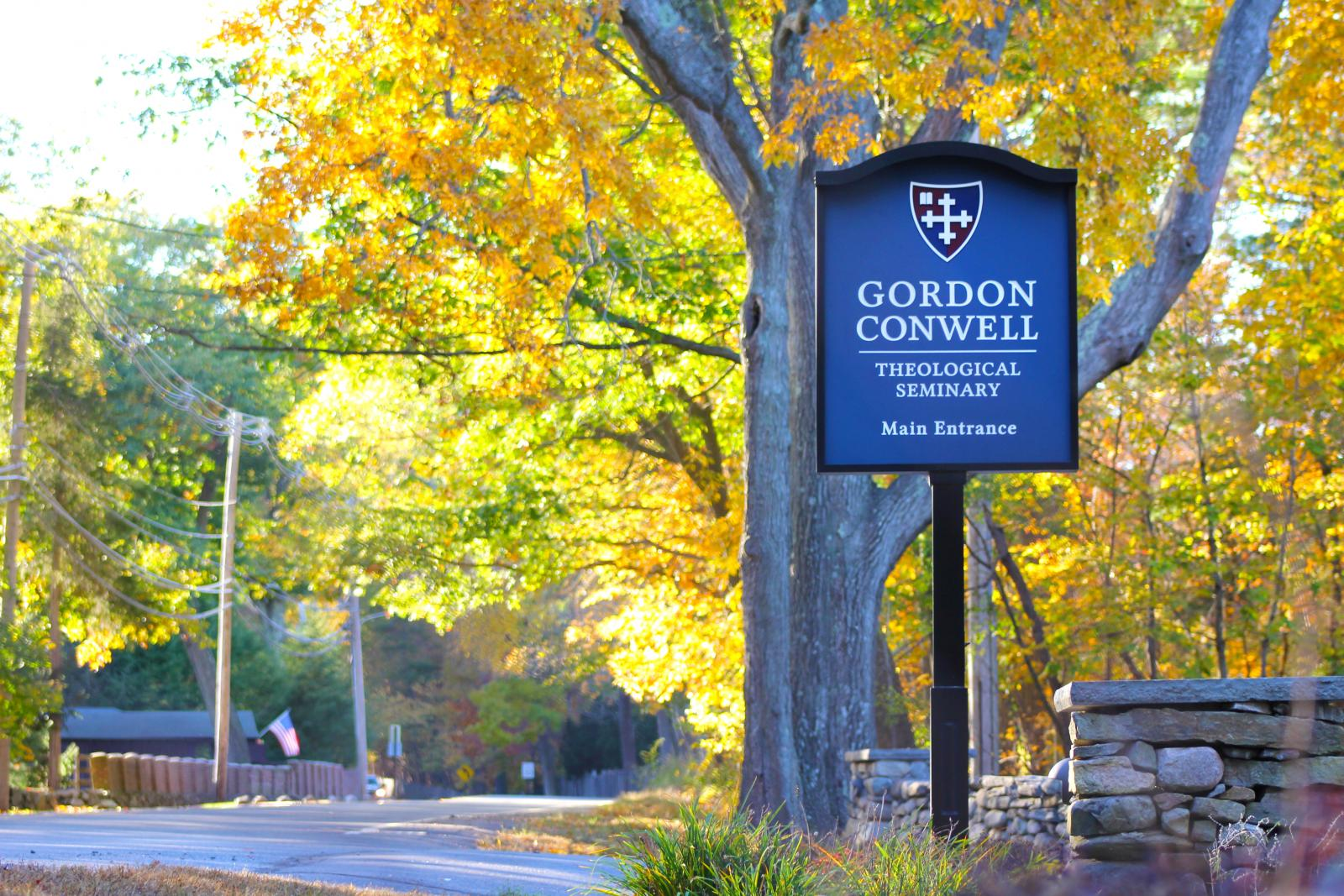 Blue and White Gordon Conwell entrance sign. Background of fall foliage.